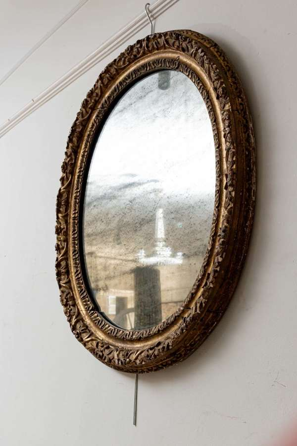 French oval C19th gilt mirror, frame is C18th.